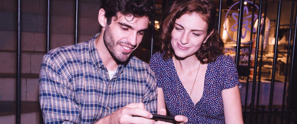 NuConta: dois jovens, um homem e uma mulher, vestindo roxo olham para a tela de um celular, segurado pelo homem.