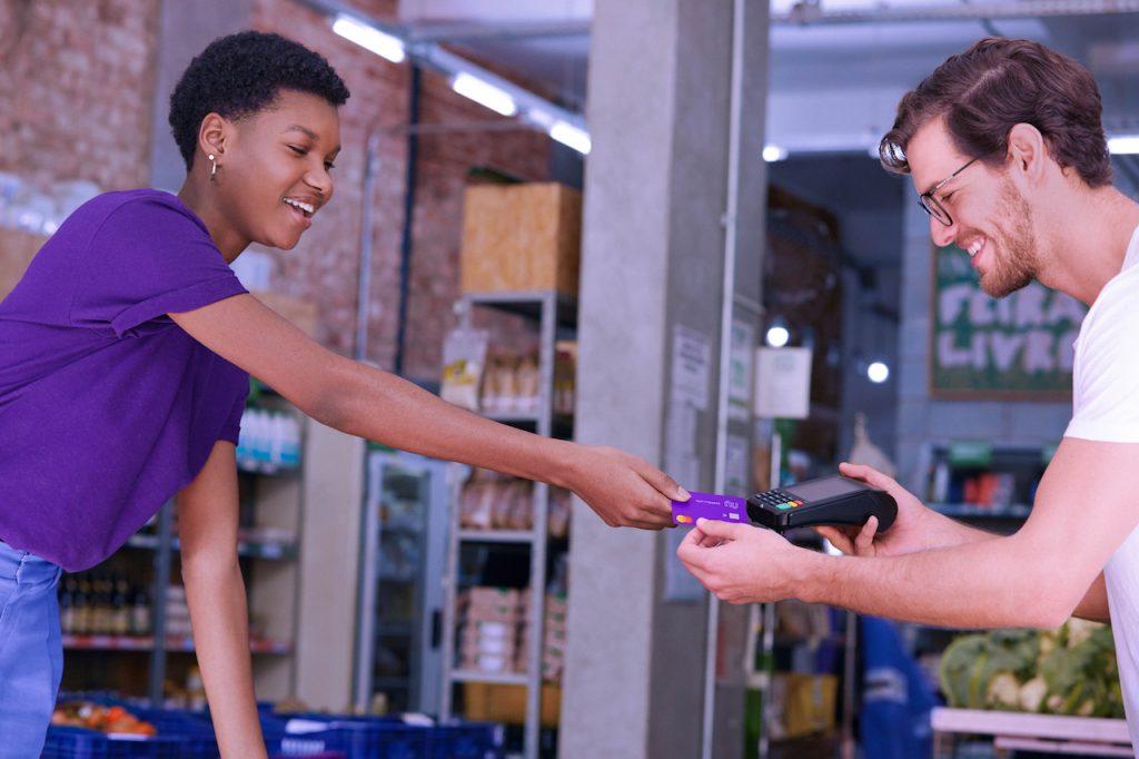 Conta PJ Nubank: numa loja, um homem com uma maquininha de cartão numa mão pega o cartão de uma cliente.