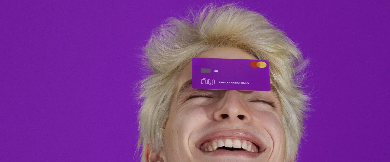 1,5 bilhão de transações header: Foto mostra um jovem em um fundo roxo com um cartão nubank equilibrado na testa