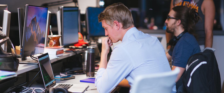 Programação Funcional: no Nubank, um homem está sentado em frente à mesa com o computador aberto. Ele está programando. Atrás, outro homem está sentado e um em pé ao lado dele.