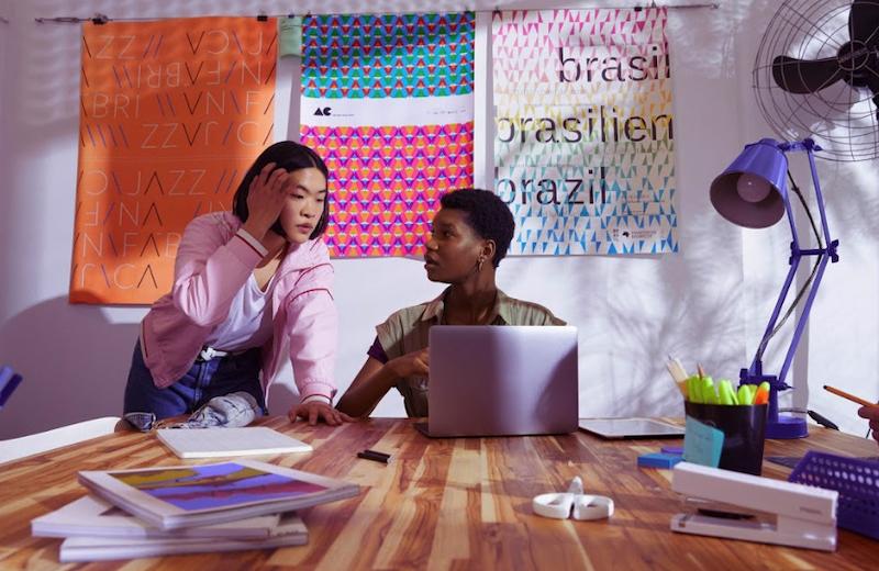 Freela: uma mulher sentada e outra de pé olhando um notebook em frente a uma mesa de escritório