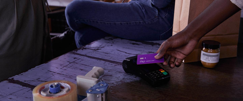 Conta PJ Nubank Novidades: no balcão de uma loja, a mão de um homem passa um cartão Nubank na maquininha. Ao lado da mão tem um pote de vela e uma sacola. Também têm um rolo de fita adesiva e um marcador. No balcão está sentada uma mulher e outra está em pé.