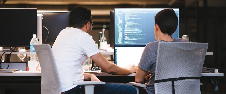 Data Science: dois homens sentados olhando para um computador. Na segunda tela, um programa de código de programação.
