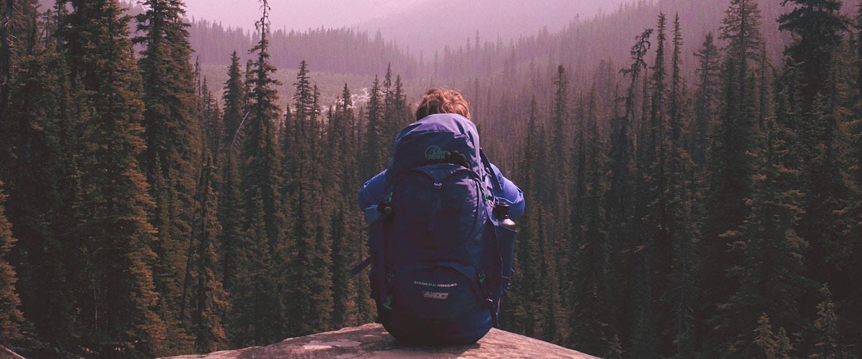 Mochilão: pessoa sentada em uma pedra com mochila roxa nas costas olhando a paisagem de árvores e montanhas