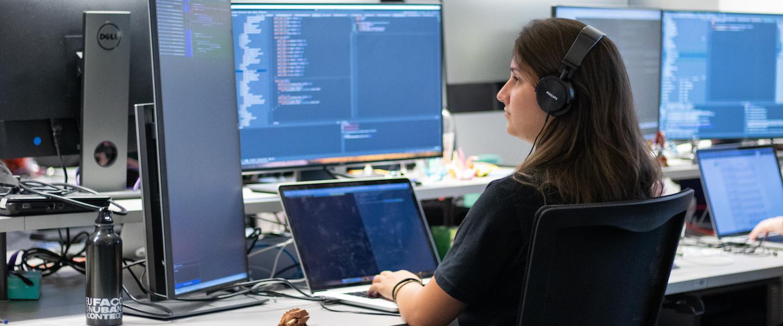 Engenharia de software Nubank: uma mulher com fones de ouvido programando. Ela está com um notebook na mesa e usa dois monitores auxiliares.