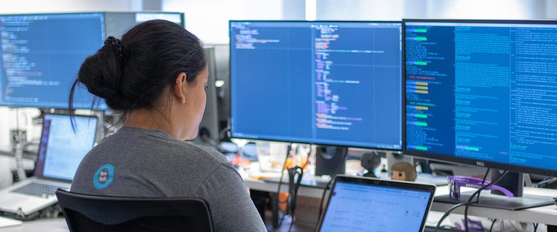 O que é Clojure: foto de uma mulher trabalhando com um notebook e dois monitores que exibem códigos de programação.
