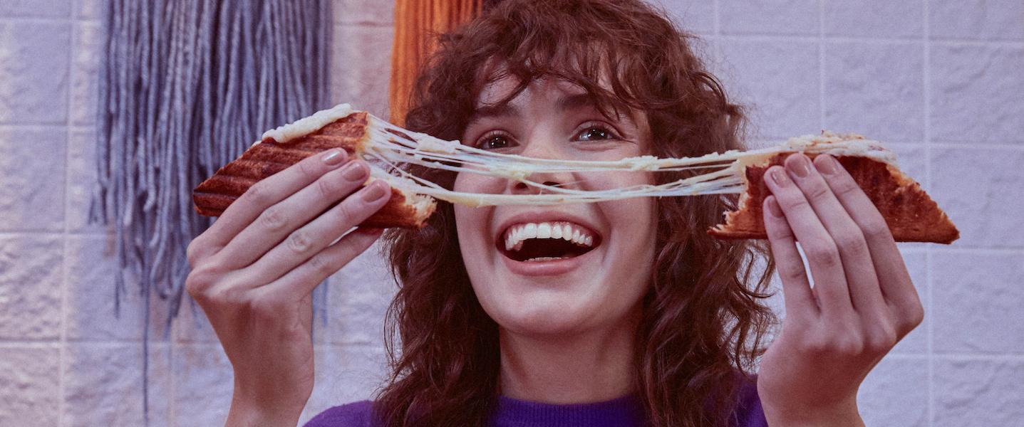 mulher sorrindo com queijo quente na mão