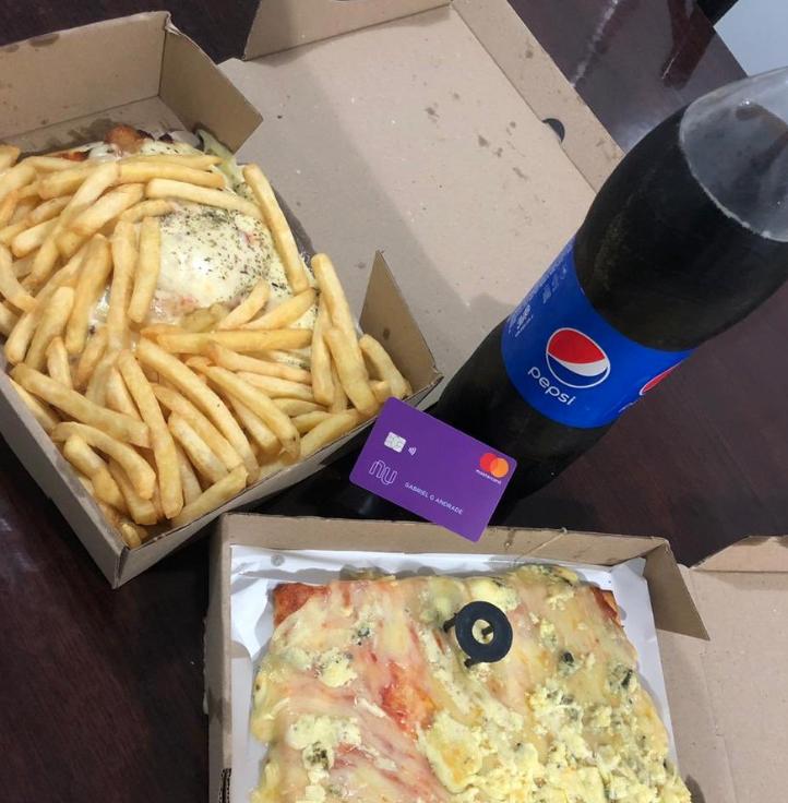 Duas pizzas e batatas fritas, ao lado de um refrigerante.
