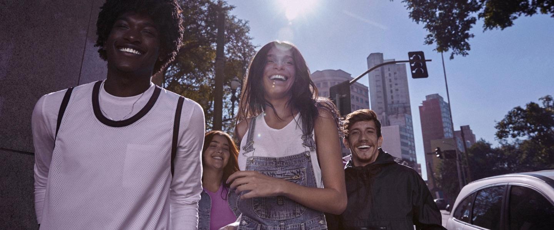 Foto mostra grupo de 4 pessoas andando na rua, sorrindo, em um dia ensolarado