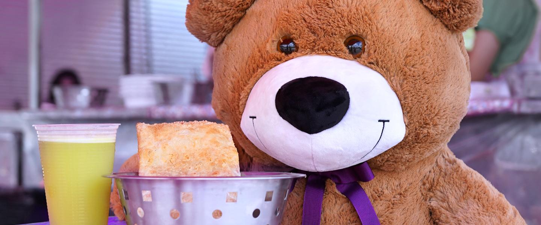 TED: o Urso TED do Nubank em uma feira de rua comendo pastel e tomando caldo de cana.