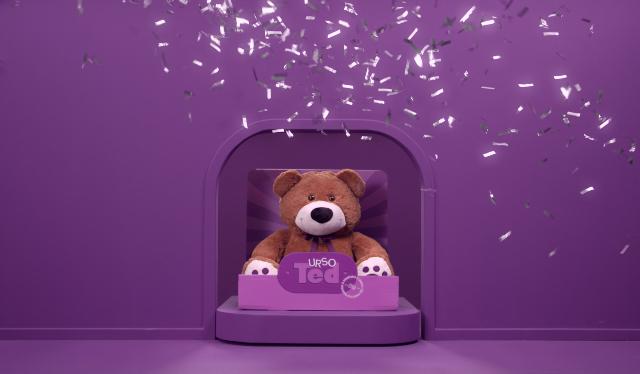 TED Bear: ursinho do Nubank em uma caixa e cenário roxo com chuva de prata caindo sobre ele