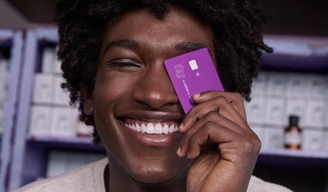 Homem sorrindo segurando um cartão de crédito Nubank na frente do rosto