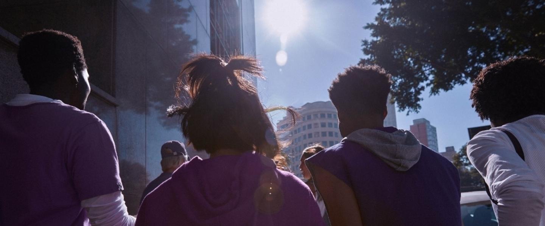 Quatro pessoas de costas andando na rua durante o dia