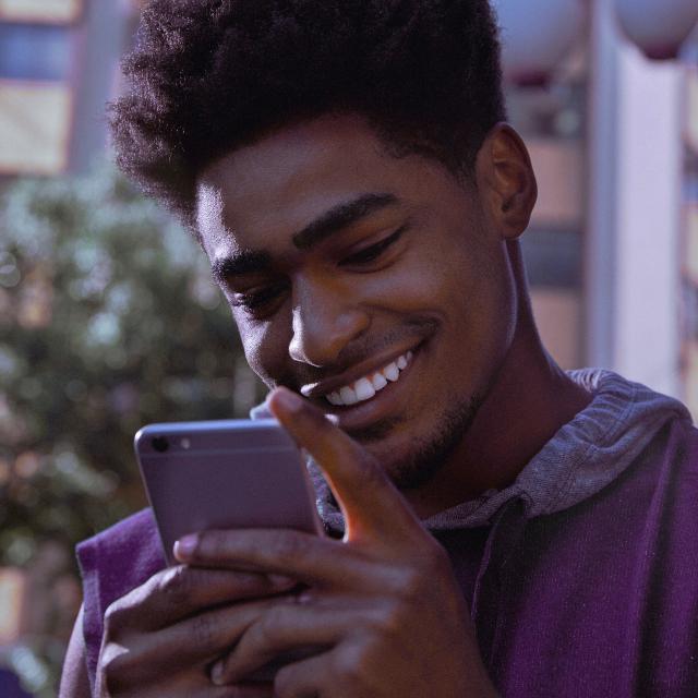 Jovem vestindo moletom roxo segura um celular em frente ao seu rosto enquanto sorri.