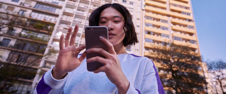 NuConta: foto mostra mãos em primeiro plano segurando um telefone