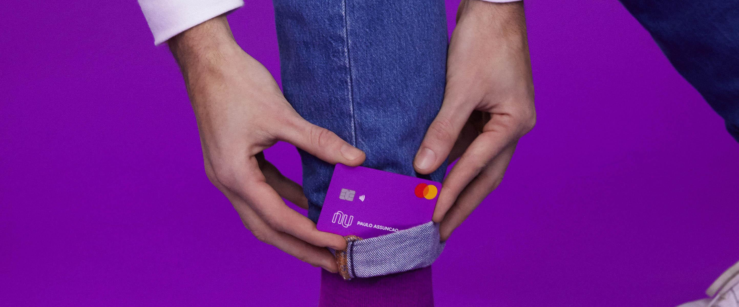 Produtos Nubank: uma pessoa vestindo uma calça jeans e tênis branco, sobre um fundo roxo, segura seu cartão Nubank do lado de sua perna.