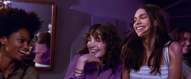 TED Nubank Horário: fotografia de três mulheres no balcão de um restaurante dando risada olhando uma para a outra.