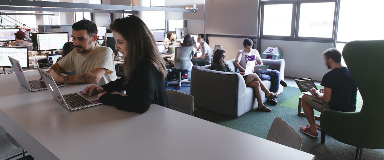 Vagas Nubank 2020: foto interna do escritório do Nubank. Num balcão, um homem e uma mulher trabalham juntos em seus computadores. Ao fundo, três pessoas conversam sentadas num sofá cinza e numa poltrona verde.