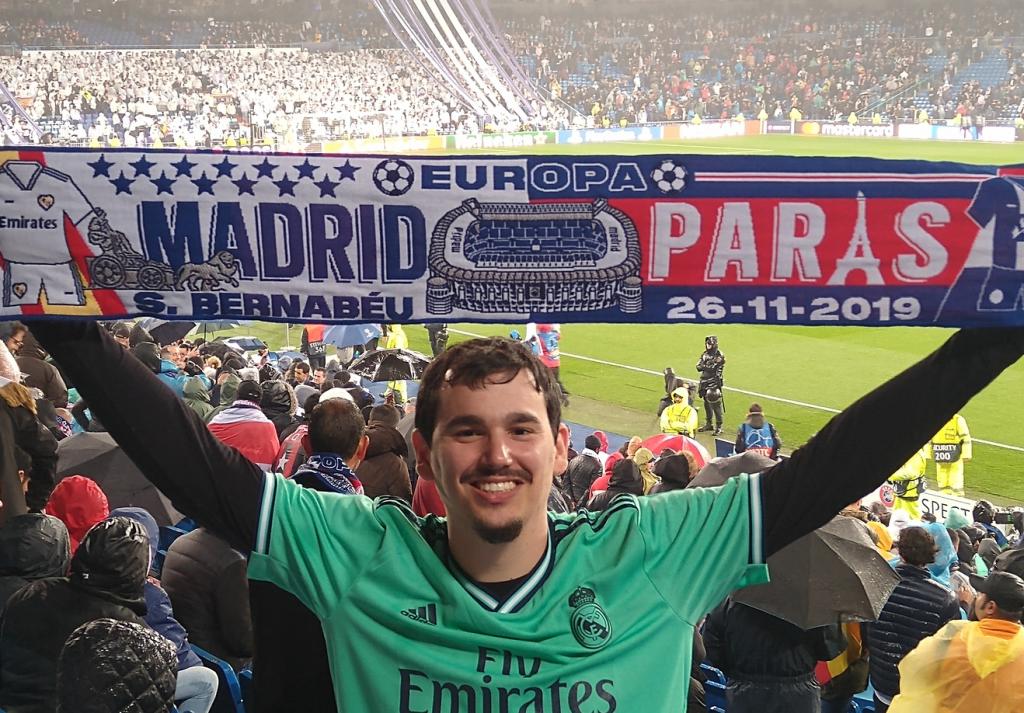 Arthur no jogo do Real Madrid, vestindo a camisa do time e segurando uma faixa de torcedor do time espanhol.
