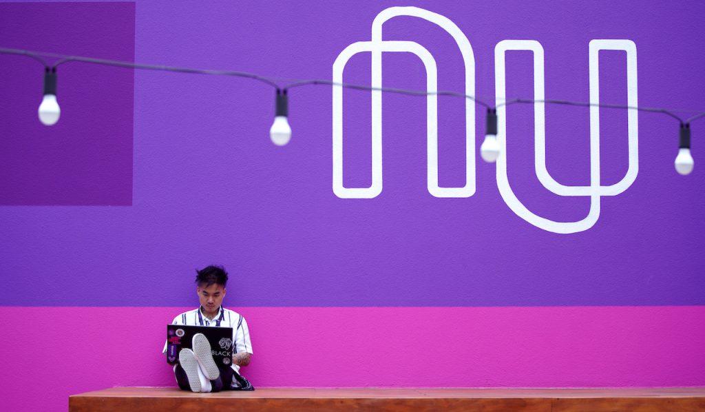 MVP: Garoto sentado em um tablado de madeira no canto esquerdo inferior da foto, segurando um notebook. Ele estáem frente aum mural rosae roxo onde está escrito NU em branco.