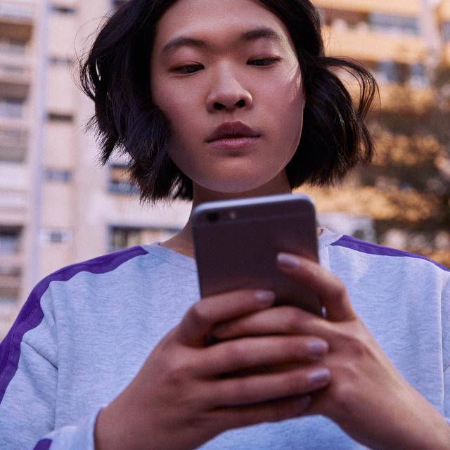 Celular roubado: garota vestindo moletom cinza e roxo segura um celular na altura do peito.