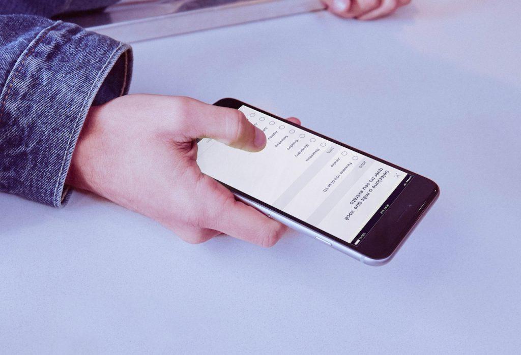 Extrato OFX Conta PJ Nubank: fotografia em close da mão de um homem segurando um celular sobre um balcão branco. Na tela, imagem da Conta PJ do Nubank.