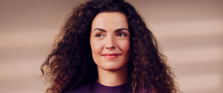 Uma mulher sentada em frente à câmera olha de lado e sorri. Ela tem o cabelo cacheado e veste uma blusa de manga comprida roxa.