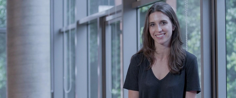 Product Manager: Foto de Aly sentada sorrindo, usando uma camiseta preta