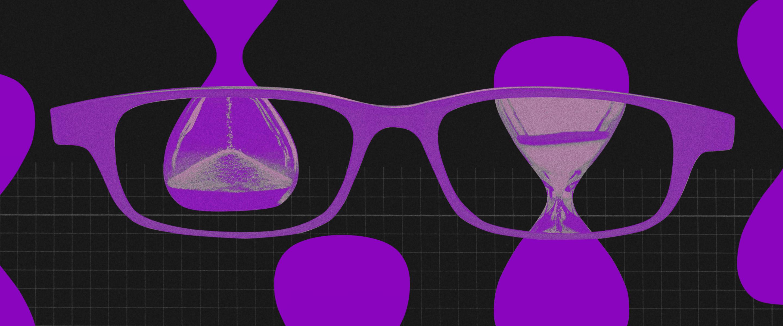 Imagem de um óculos de armação roxa em frente a uma ampulheta também roxa. Os dois estão num fundo preto.