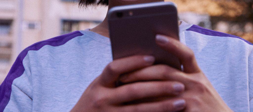 Higienizar celular: garota vestindo moletom cinza e roxo segura um celular na altura do peito.