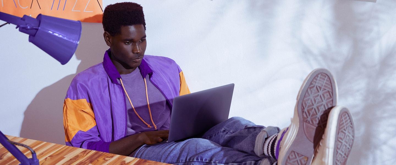 Online: Homem vestindo jaqueta roxa sentado com os pés sobre a mesa e trabalhando em um notebook