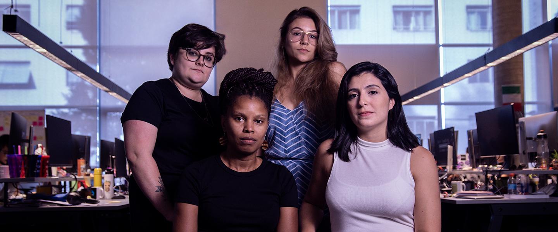 Mulheres no Nubank: imagem de quatro mulheres olhando para a câmera. As duas da frente estão sentadas, as de trás estão de pé.