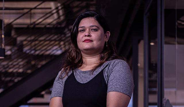 Mulheres Nubank: fotografia de Kete, líder técnica no Nubank, posando de pé no escritório. Ela veste macacão preto de alçar e camiseta cinza.