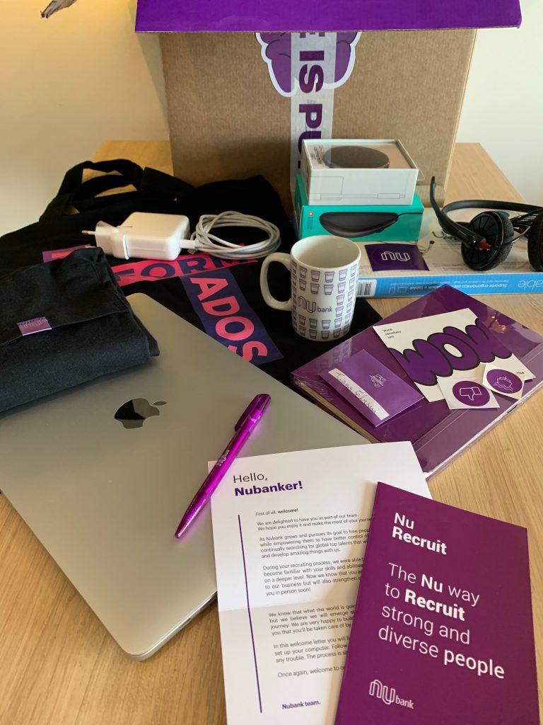 Onboarding remoto Nubank: imagem do kit de boas-vindas que Nubank enviou aos novos funcionários, contendo computador, caderno, camiseta