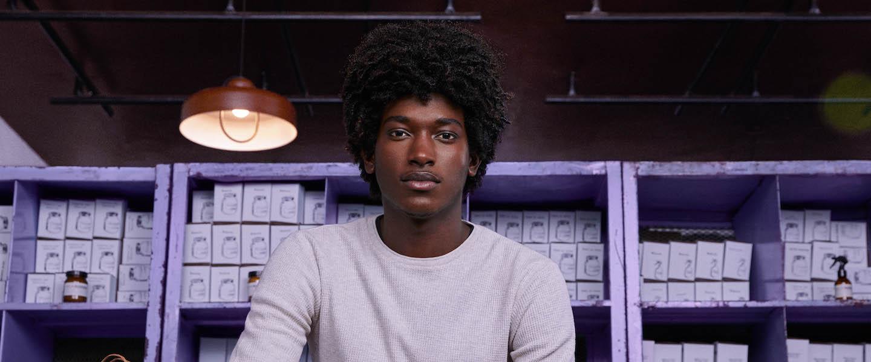 Nubank: homem sentado olhando para frente, vestindo uma camiseta cinza de manga comprida