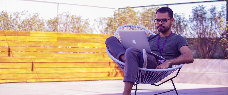 Onboarding remoto Nubank: homem sentado em uma cadeira num terraço com o computador no colo.
