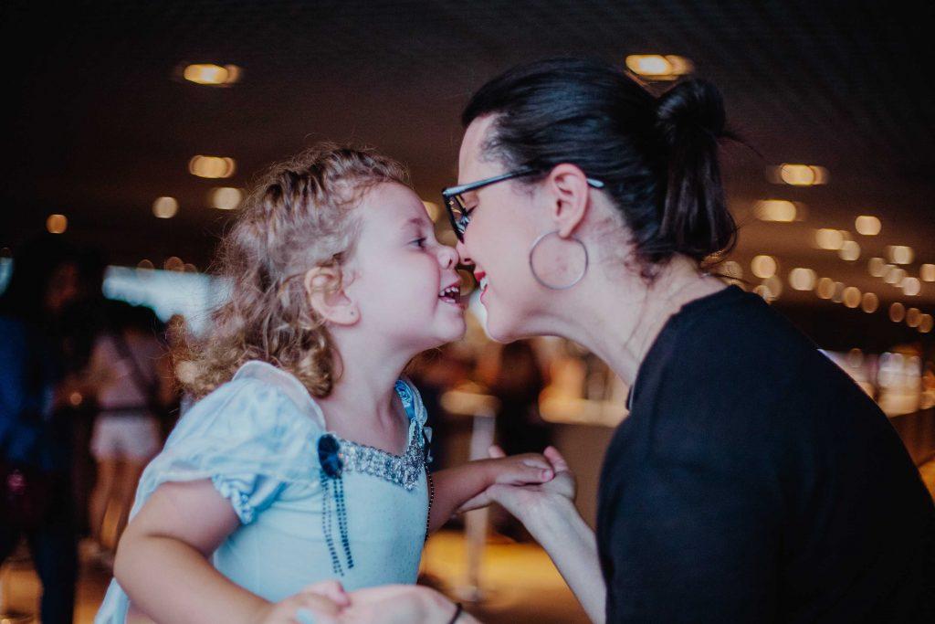 Damaris encostando o nariz no nariz de sua filha, Rebecca. Ambas sorrindo.