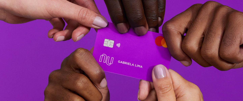Nubank 30 mil clientes 60 anos : no fundo roxo, cinco mãos seguram o cartão Nubank