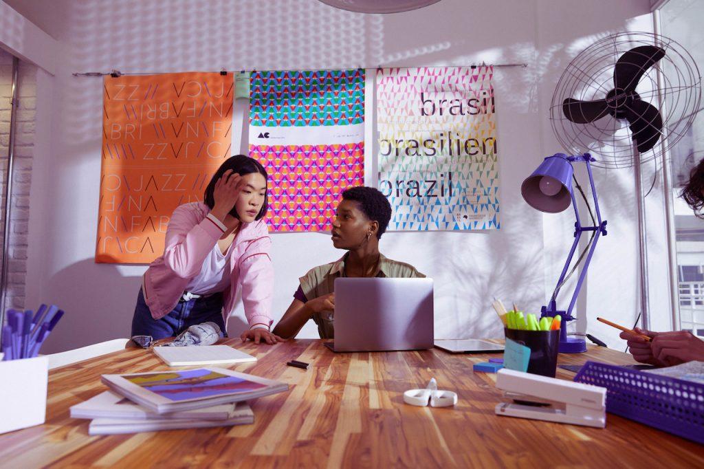Conta PJ Nubank: foto mostra duas jovens conversando em frente a uma parede de post its. Uma delas está sentada em uma mesa, com um computador aberto