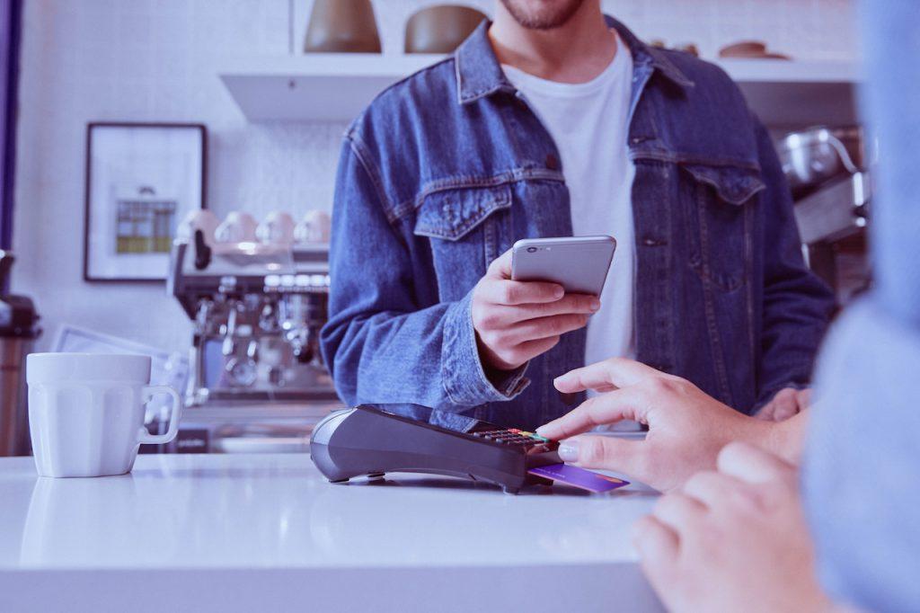 Conta PJ Nubank: Conta PJ Nubank: imagem mostra jovem de óculos e jaqueta jeans, atrás de um balcão de café, olhando para o telefone