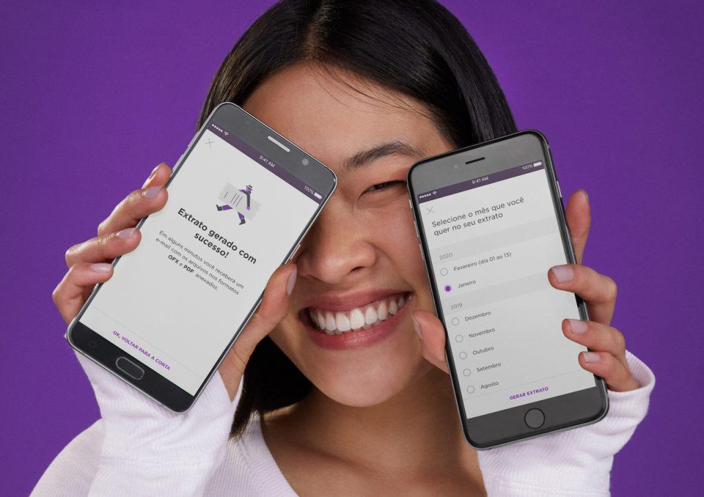 Conta PJ Nubank: fotografia de estúdio, no fundo roxo, de uma mulher oriental segurando dois celulares nas mãos. Nas telas, imagens da Conta PJ do Nubank.