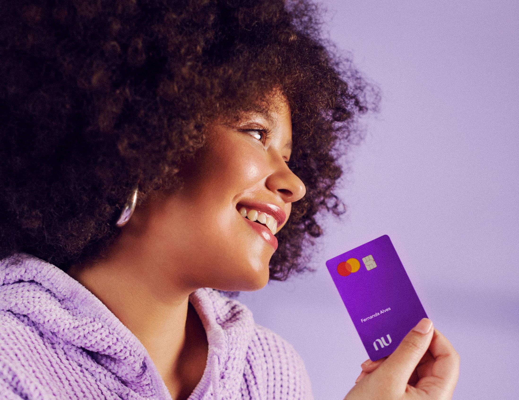 mulher sorrindo, vestindo uma blusa lilás e segurando o cartão Nubank