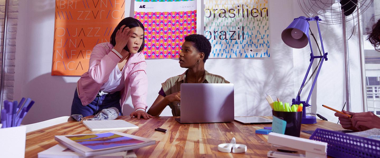 Boleto de cobrança e boleto de depósito: foto mostra duas jovens conversando em frente a uma parede de post its. Uma delas está sentada em uma mesa, com um computador aberto
