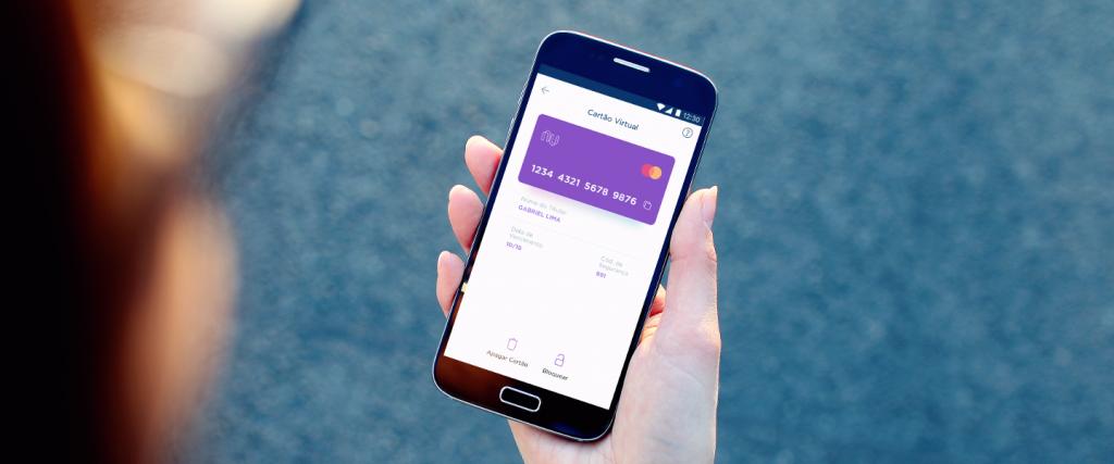 Cartão virtual na função débito: Mão segura um telefone. Na tela, a imagem da tela do app Nubank com cartão virtual e sua numeração .