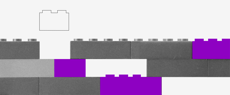 Imagem de peças de lego empilhadas. Uma peça branca paira acima, prestes a ser encaixada