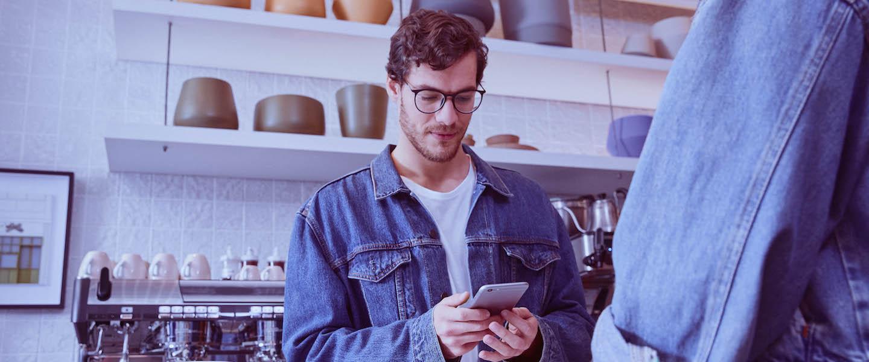 Atualização cadastral Nubank: imagem mostra jovem de óculos e jaqueta jeans, atrás de um balcão de café, olhando para o telefone