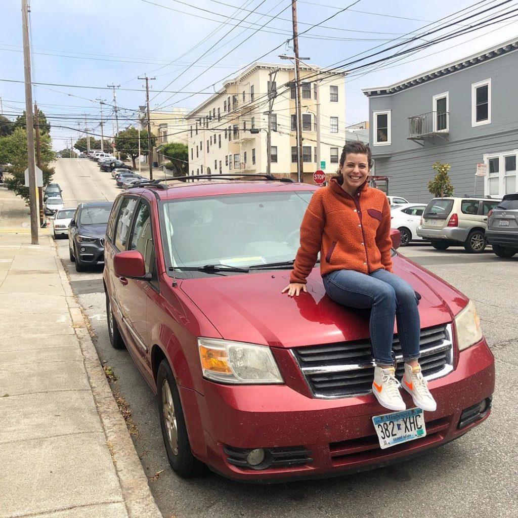 Imagem de Demi sentada sobre o capô de um carro vermelho estacionado na rua