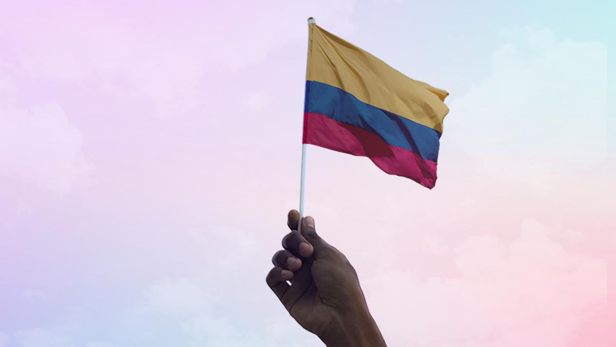 Mão segurando uma bandeira colombiana