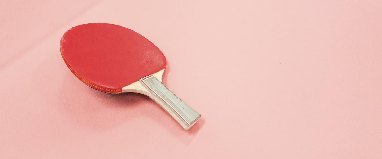Auxílio emergencial ciclo 2 nascidos dezembro: fotografia de uma raquete de ping pong em um fundo coral