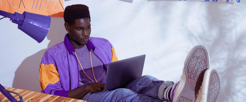 CLT ou PJ: Homem vestindo jaqueta roxa sentado com os pés sobre a mesa e trabalhando em um notebook